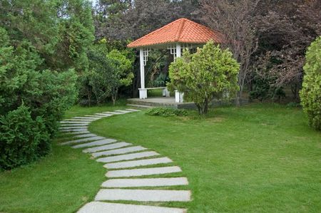 Sumerhouse and curving walkway in the garden photo