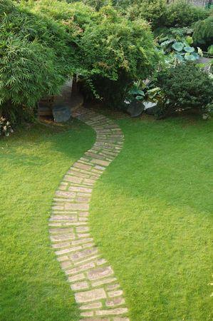 tuinhuis: Rustige tuin stenen weg met gras en bomen die opgroeien in een zomerhuisje in de ochtend