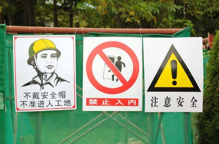 Warning Prohibited and keep out sign at a construction area in China.From right to left, it means 1)Safety caution,2) Keep out,3)Keep out without motorcycle safety helmet  photo