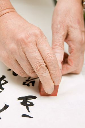 a person at a desk using a agalmatolite stamp or  seal on his Chinese calligraphy work  Stock Photo - 3645723