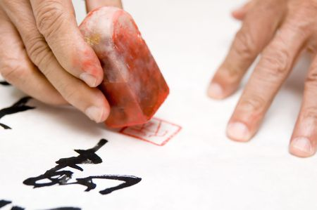 a person at a desk using a agalmatolite stamp or  seal on his Chinese calligraphy work  photo