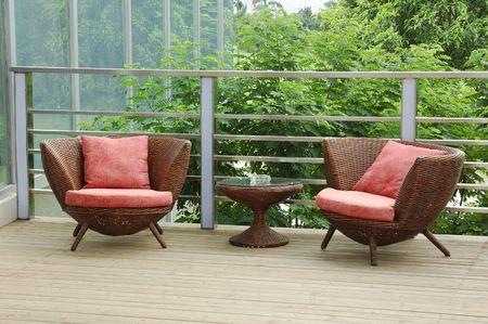 patio furniture: Sedie di vimini sul patio in un bellissimo giardino. Archivio Fotografico