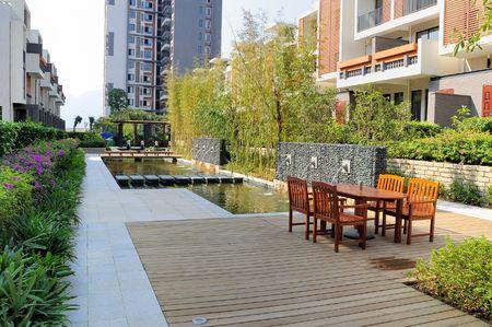 baranda para balcon: Paisaje al aire libre con sillas de descanso y fuente y árboles en un nuevo barrio residencial Foto de archivo