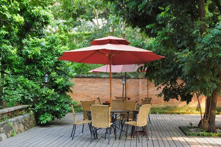 outdoor cafe: Summer Patio with tables and cane chairs under umbrella in China Stock Photo