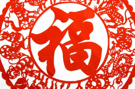 decoupage: Traditional Chinese Paper-cut for celebration of Spring Festival or Wedding, very popular in Chinese family.The pronunciation of the word in the centre is fu, means good fortune. Stock Photo