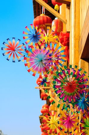 pinwheel: Colorful rainbow toy pinwheels and red lantern hanging in a small market in China Stock Photo