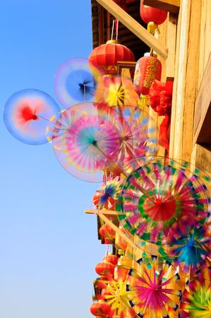 Turning colorful rainbow toy pinwheels and red lantern hanging in a small market in China Stock Photo - 4321752