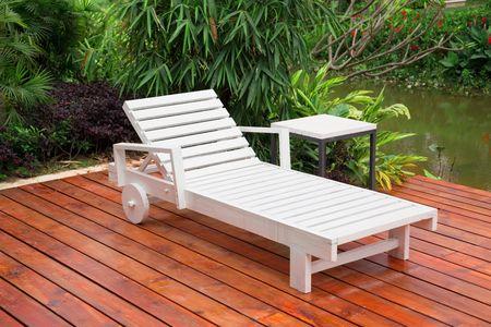 deck: Wooden reclining chair in a garden