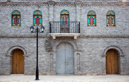 Detail of old Chinese style building facade with arch doors and colorful windows in a town.This is  architectural style  in the begin of last century's. Stock Photo - 5111786