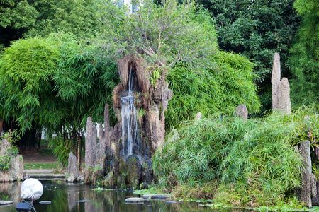 Chinese rockery with bamboo and pond around in a garden. The rock of rockery is famous taihu stone  photo