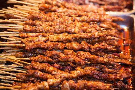 Roasted meat on wood sticks prepared for eating photo