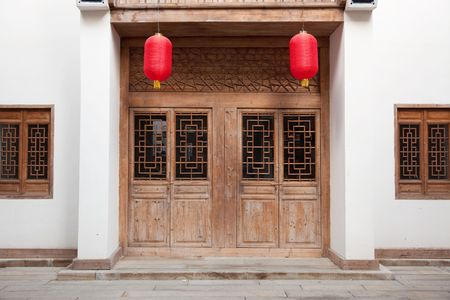 wood pillars: Detail of old Chinese style building facade with wooden door and  windows in a town.This is architectural style in the begin of last centurys. Stock Photo