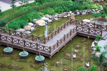 Zig-zag wooden bridge through a tranquil garden photo