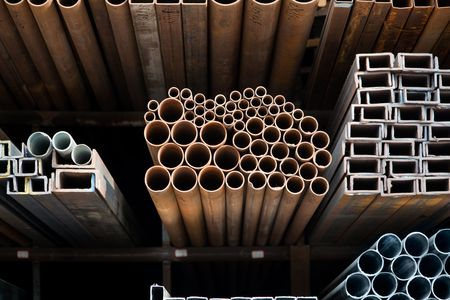 A series of different sizes metal pipes on  shelf.Soft focus on metal surface photo