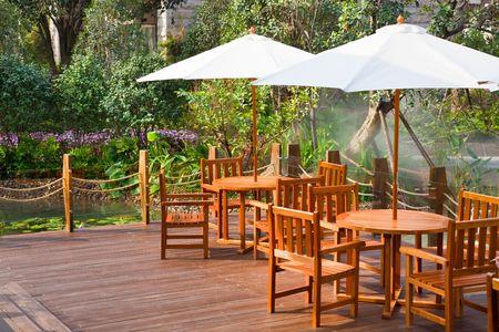 현관: 우산 아래 테이블과 의자가있는 집 안뜰