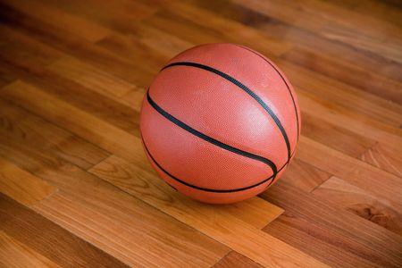 Basket-ball sur le sol de basket-ball de feuillus dans un stade