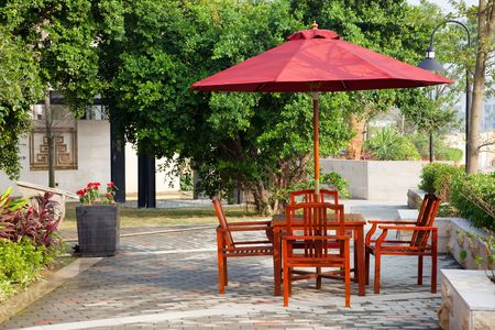 Summer Patio with tables and wooden chairs under umbrella in garden photo