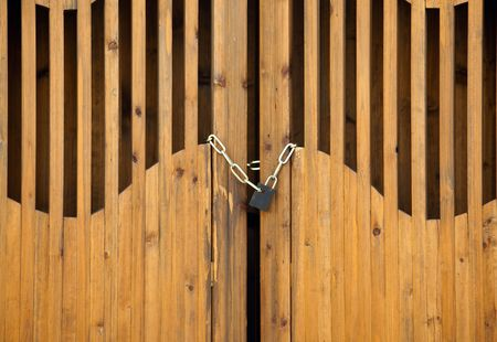Closed wooden door with ornamental barricade and padlock photo