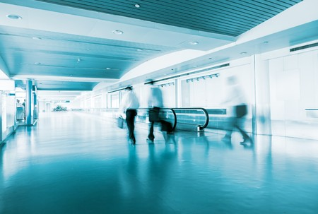 People Walking in Airport Tunnel with moving walkway, long exposure photo