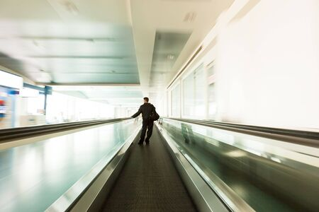 elevator: Rush at the airport escalator with unrecognizable people walking on, long time exposure.