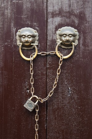 Old Chinese style  door with iron chain and  mythical wild animal head door handles. photo