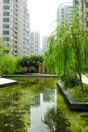 tuinhuis: Centrale tuin met vijver water en zomerhuis in een nieuwe Chinese woonwijk