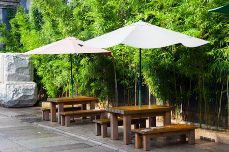 cafe table: Asian cityscape: wooden table and bench under sunshade against bamboo tree. This is prepare for the tourist  and citizen in summer.