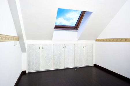 slanted: New modern attic room with a roof skylight window and wall cabinet