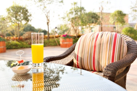 Glass of orange juice and ice cream on table in a garden. photo