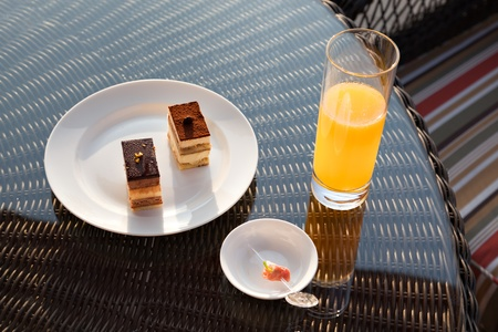 Glass of orange juice and ice cream on rattan table. photo