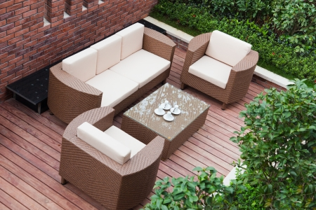 Home exterior patio with wooden decking and rattan sofa view from the top.