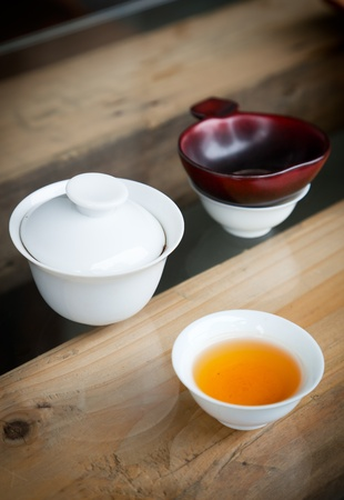 Simple Chinese tea set - small teacup,teabowl and  tea  filter on wooden table  photo