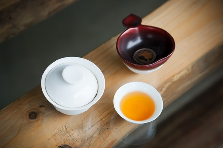 tea filter: Simple Chinese tea set - small teacup,teabowl and  tea  filter on wooden table