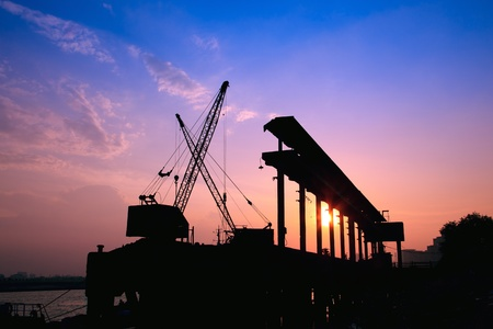 Silhouette of several cranes working at sunset in a harbor photo