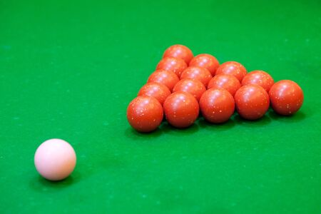 Red snooker balls  and pink on a green baize table photo