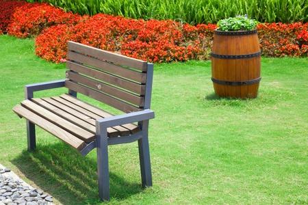 Beautiful summer garden with bench and big decorative wooden flowerpot photo