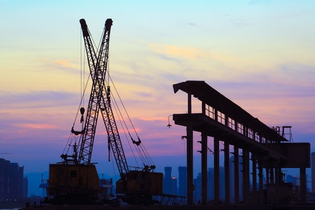 rive: Silhouette of several cranes working at sunset in a harbor