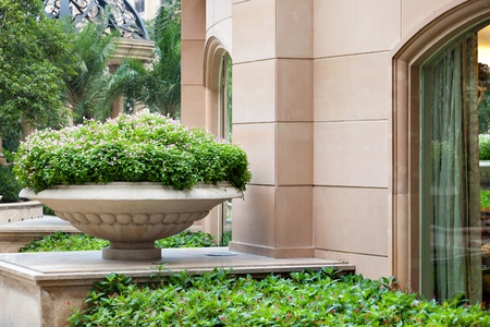 Big stone parkgarden flowerpot with ornament and evergreen plant  in garden Stock Photo