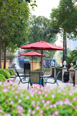 outdoor cafe: Summer Patio with tables and wooden chairs under umbrella in garden