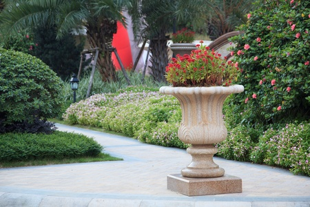 Ornamental  stone flowerpot in garden.The flower on vase is called Chi kuan in China. photo