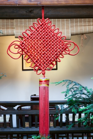 knotting: Chinese festal knotting hanging on wooden beam in a traditional Chinese patio