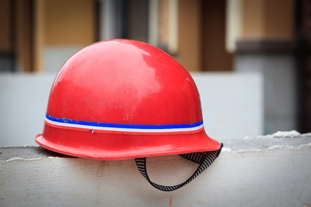 lagging: Red hard hat on a wall at a constuction site Stock Photo