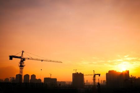 cantieri edili: Silhouette della gru a torre in cantiere con sfondo edificio della citt� Archivio Fotografico