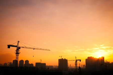 unfinished building: Silhouette of the tower crane on the construction site with city building background