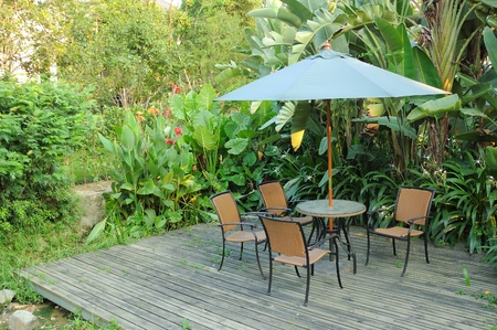 Garden furniture - rattan chairs and table under umbrella on a wooden floor by the banana trees background in garden
