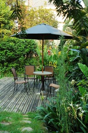 malacca: Mobili da giardino - sedie in rattan e tavolo sotto l'ombrello su un pavimento di legno in giardino