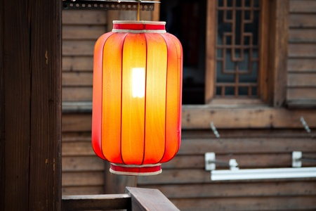 Hanging red lantern on the pillar by the traditional wooden wall background Standard-Bild