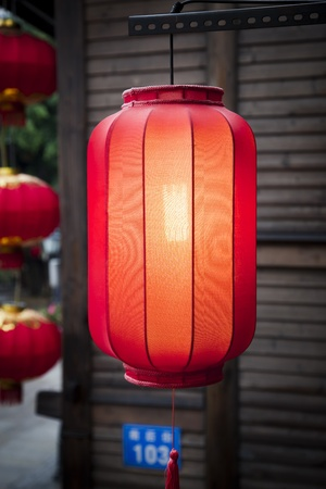 Hanging red lantern on the traditional wooden wall background in a Chinese market photo