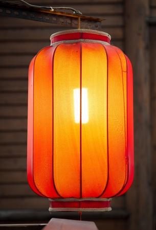 muralla china: Pendiente linterna roja en el fondo de la pared de madera tradicional