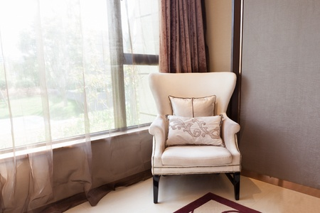 Armchair close to  the window at  a new interiors, through the window  a small garden can be seen  Standard-Bild